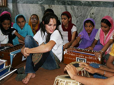 Angelina Jolie, in New Delhi for the weekend as a UNHCR Goodwill Ambassador, listens to Sikh children playing religious music at the Khalsa Diwan Welfare Society, an organization run by and for Afghan refugees, on Saturday.