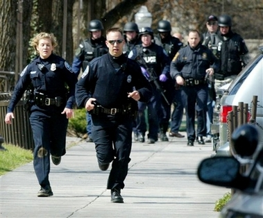 Blacksburg police officers run from Norris Hall on the Virginia Tech campus in Blacksburg, Va., Monday, April 16, 2007. Multiple shootings occurred at the engineering building on Monday. A gunman opened fire in a Virginia Tech dorm and then, two hours later, in a classroom across campus Monday, killing at least 30 people. (AP Photo/The Roanoke Times, Matt Gentry)