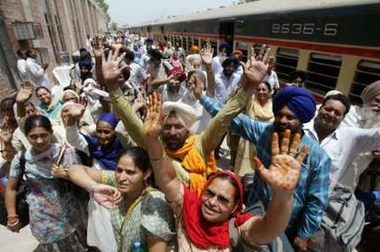 Indian Sikh pilgrims wave on arrival in Pakistan at Wagah railway station near Lahore June 13, 2006. About 400 Sikh pilgrims arrived in Pakistan to take part in the 400th martyrdom day celebrations of the fifth Guru of Sikhism, Guru Arjun Dev Jee, scheduled to be held at Gurdawara Dera Sahib in Lahore from June 13 to 16. REUTERS/Mohsin Raza (PAKISTAN)
